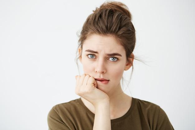 Mooie verlegen jonge vrouw met haar broodje denken bijten lip.