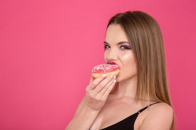Mooie verleidelijke aantrekkelijke sensuele jonge vrouw die zoete roze smakelijke doughnut over roze muur eet