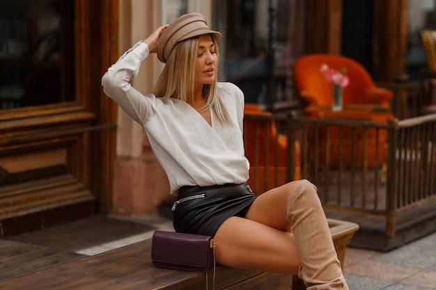 Mooie verleidelijke blonde vrouw zittend op de bank