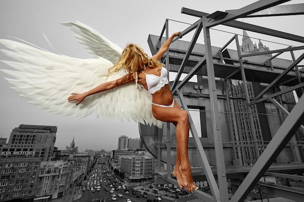 Mooie verleidelijke engelenvrouw die lingerie draagt die op het dak in grote stad met wind in haar vleugels over bewolkte hemel gehurkt zit