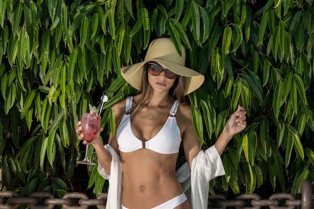 Mooie verleidelijke vrouw in bikini met cocktail