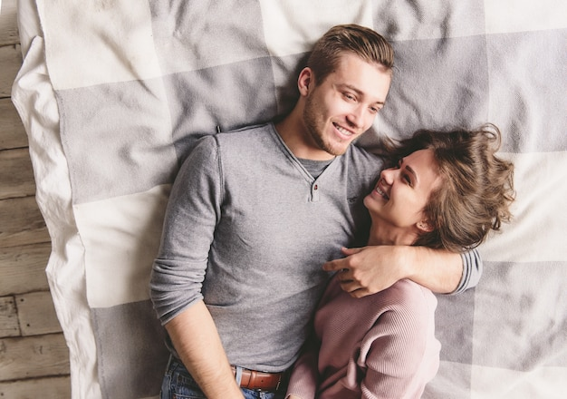 Mooie verliefde paar is luxuriating in bed samen. ze knuffelen en glimlachen