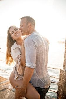 Mooie verliefde paar knuffels en kusjes onder de stromen van water in een luxe spahotel op hun huwelijksreis, vakantie in de tropen. selectieve focus