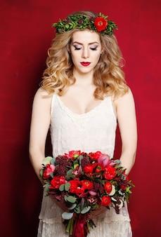 Mooie verloofde in witte jurk en bloemen op rode achtergrond