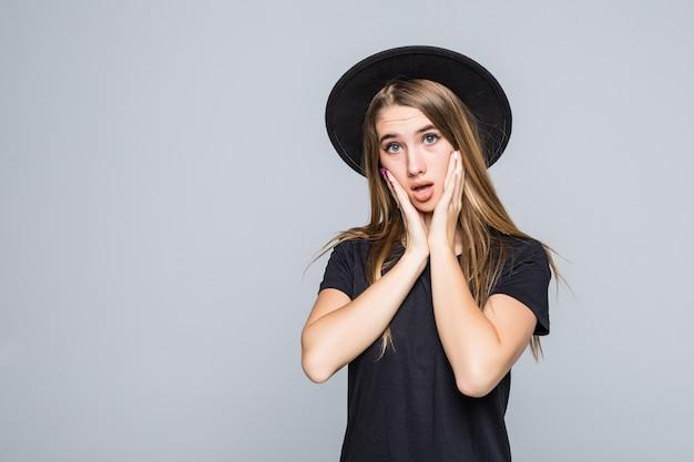 Mooie verloren jonge vrouw model toont emoties gekleed in donkere kleding geïsoleerd op een grijze achtergrond