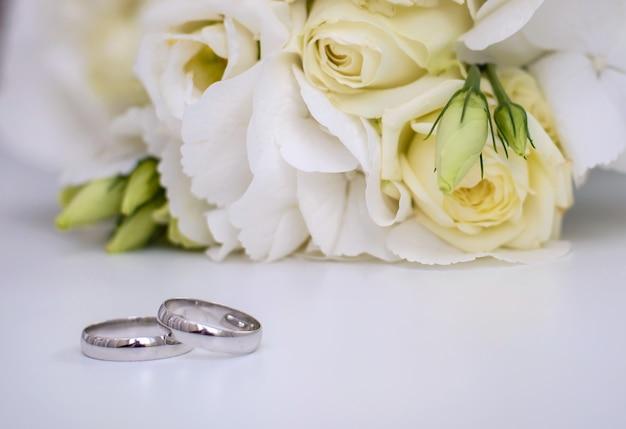 Mooie verlovingsringen en bruidsboeket van witte bloemen op een witte ondergrond