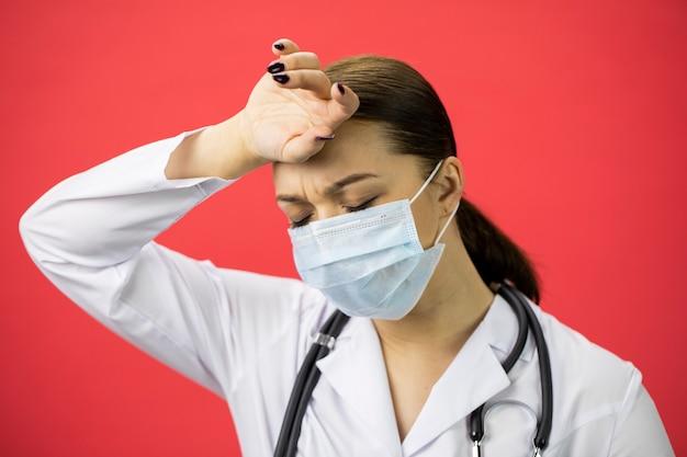 Mooie vermoeide vrouwelijke arts in beschermend masker dat aan hoofdpijn lijdt