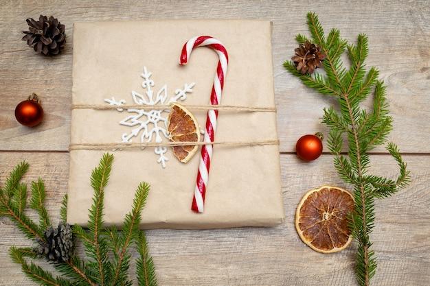 Mooie verpakte geschenkdoos met dennentakken, snoepgoed, decor op houten achtergrond. kerstversiering, nieuwjaar plat lag, bovenaanzicht plat, overhead.