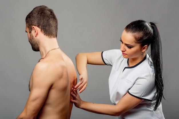 Mooie verpleegster die terug een grijze mens onderzoekt. de donkerbruine vrouw arts in witte medische laag controleert de rug van de patiënt.