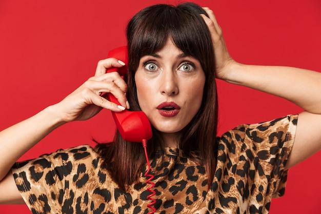 Mooie verraste jonge vrouw gekleed in een shirt met dierenprint poseren geïsoleerd over rode muur praten via de telefoon.