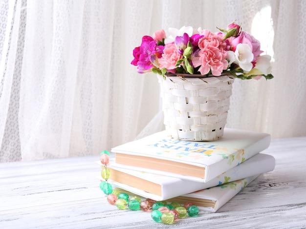 Mooie verse lentebloemen met stapel boeken op gordijnoppervlak