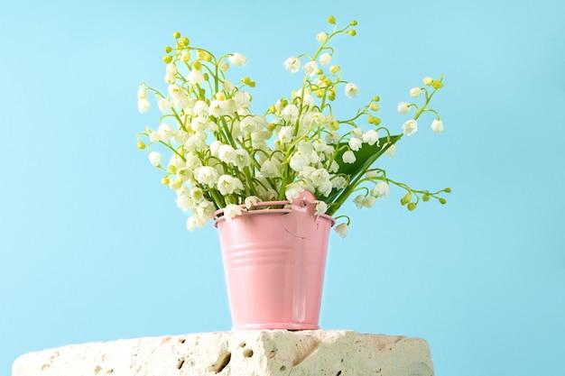 Mooie verse meilelies in de roze speelgoedemmer blijven op het cementpodium heldere blauwe achtergrond erachter