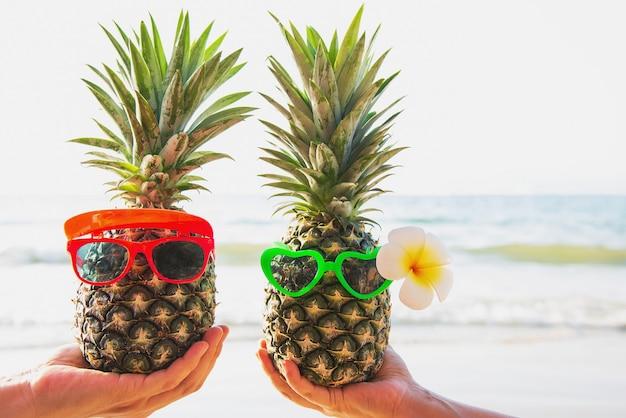 Mooie verse paarananas die glazen in toeristenhanden zetten met overzeese golf - gelukkige liefde en pret met gezond vakantieconcept
