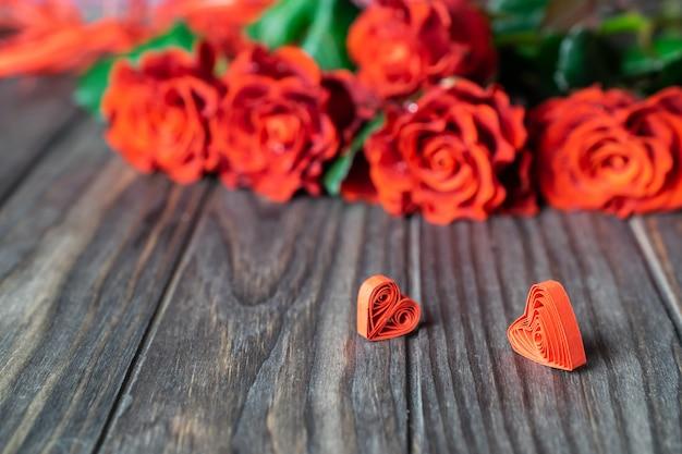 Mooie verse rode rozen met twee kleine quilled harten op hout