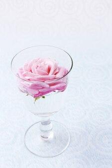 Mooie verse roos in glas op kleur behang achtergrond