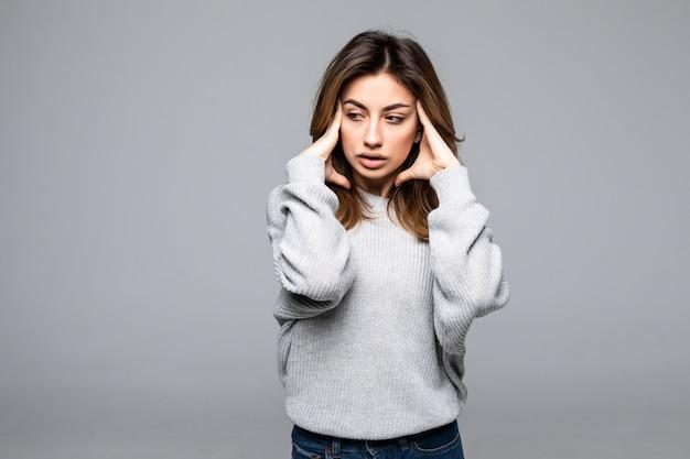 Mooie verstoorde jonge vrouw die sweater status draagt, die aan een hoofdpijn lijdt die over grijze muur wordt geïsoleerd