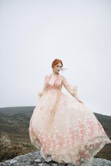 Mooie verticale foto van een roodharig vrouwtje met een puur witte huid in een aantrekkelijke roze jurk