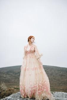 Mooie verticale opname van een roodharig vrouwtje met een puur witte huid in een roze jurk
