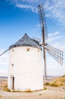 Mooie verticale opname van een witte stenen windmolen op een blauwe lucht in consuegra, spanje