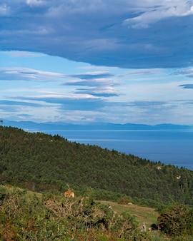 Mooie verticale weergave van blauwe lucht met wolken, zee en groene bomen aan de kust
