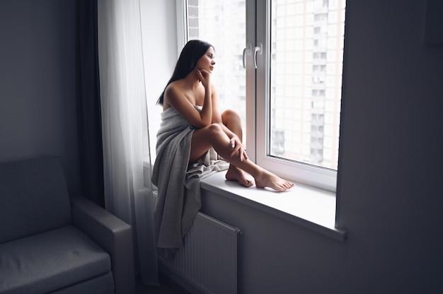 Mooie verveelde slanke donkerbruine vrouwenzitting naast venstervensterbank onder warme grijze deken thuis. zelfisolatie in quarantaine tijdens de pandemie van het corona-virus. covid19 blijf thuis, red levensconcept