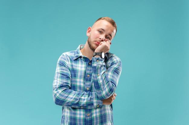 Mooie verveelde verveelde mens geïsoleerd op blauwe muur
