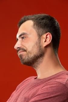 Mooie verveelde verveelde mens geïsoleerd op rode muur
