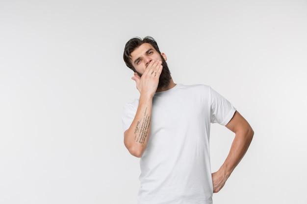 Mooie verveelde verveelde mens geïsoleerd op witte muur