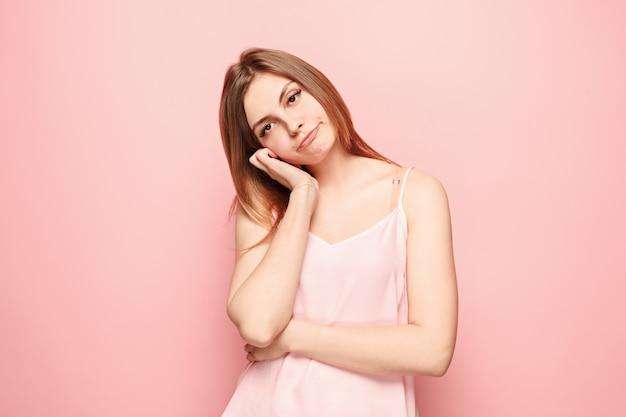 Mooie verveelde verveelde vrouw geïsoleerd op roze muur