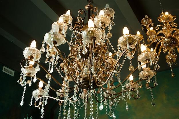 Mooie vintage kristallen kroonluchter in een kamer, gouden tinten.