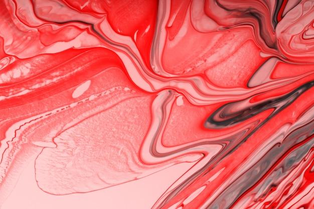 Mooie vloeibare textuur van de nagellak. zwart-wit rode achtergrond met kopie ruimte. vloeibare kunst, giettechniek. goed als digitaal decor.