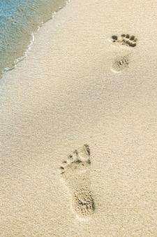 Mooie voetafdrukken met voeten op de zandachtergrond