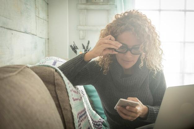 Mooie volwassen blanke vrouw thuis met behulp van technologische apparaten zoals mobiele telefoon en laptop