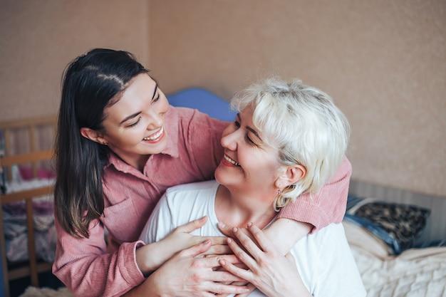 Mooie volwassen blonde moeder en haar volwassen brunet dochter knuffelen