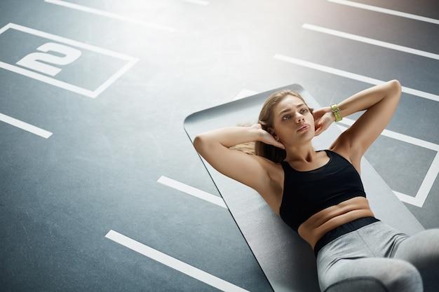 Mooie volwassen fit vrouw doet abs crunches om haar lichaam klaar te maken voor de zomer. gezond sportconcept.