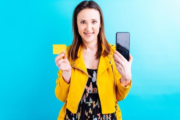 Mooie volwassen jonge vrouw met vlinders zomerjurk en gele jas op blauwe achtergrond met smartphone en creditcard. e-commerce internet shopping concept. kopen met smartphone