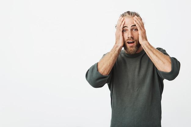 Mooie volwassen man met baard hand in hand op hoofd met gelukkige opwinding