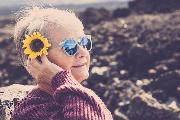 Mooie volwassen oude vrouw met gele zonnebloem op zijn hoofd neemt de zon en geniet van de levensstijl in de buitenlucht.