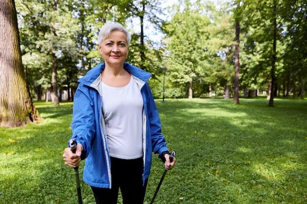 Mooie volwassen sportvrouw geniet van haar actieve hobby, houdt stokken vast voor scandinavisch wandelen, heeft een fit lichaam, brengt pensioendagen door met gezonde activiteiten. zomer, sport en vrije tijd