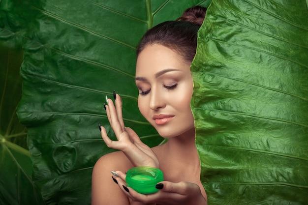 Mooie volwassen vrouw die groene roomfles voor haar mooi gezicht houdt.