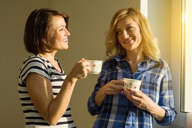 Mooie volwassen vrouw die hete koppen van koffie het drinken houdt