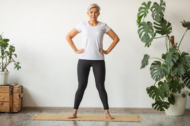 Mooie volwassen vrouw doet yoga thuis in wit t-shirt