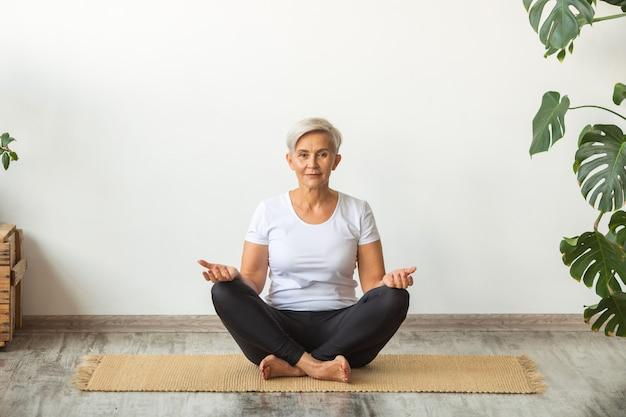 Mooie volwassen vrouw doet yoga thuis
