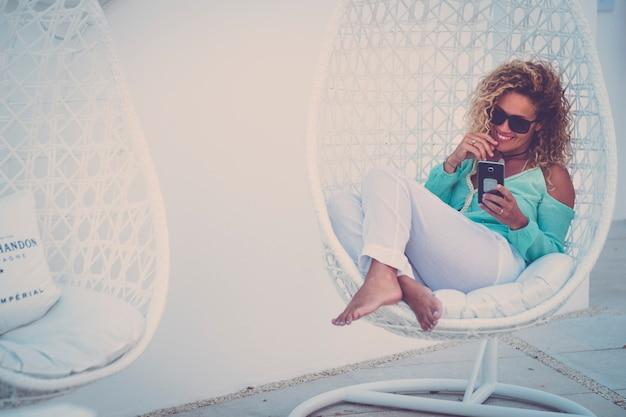 Mooie volwassen vrouw gaat zitten op een witte comfortabele stoel in de buitentuin glimlachend en met behulp van mobiele telefoon om te videobellen - mensen luxe vakantie vrije tijd concept levensstijl
