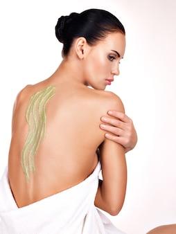 Mooie volwassen vrouw geeft om de huid van het lichaam met behulp van cosmetische scrub op de rug