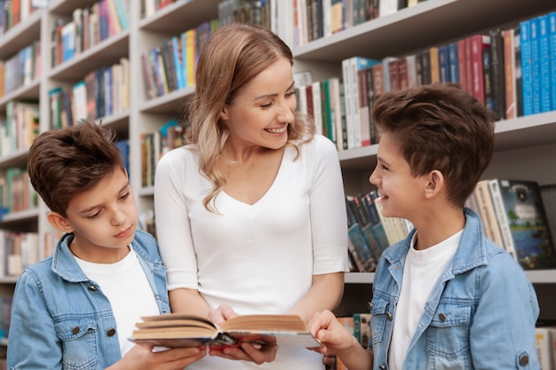 Mooie volwassen vrouw genieten van het lezen van een boek aan haar schattige kleine tweelingzonen