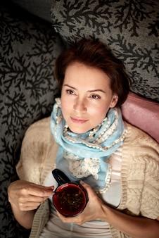 Mooie volwassen vrouw het drinken van thee in bed