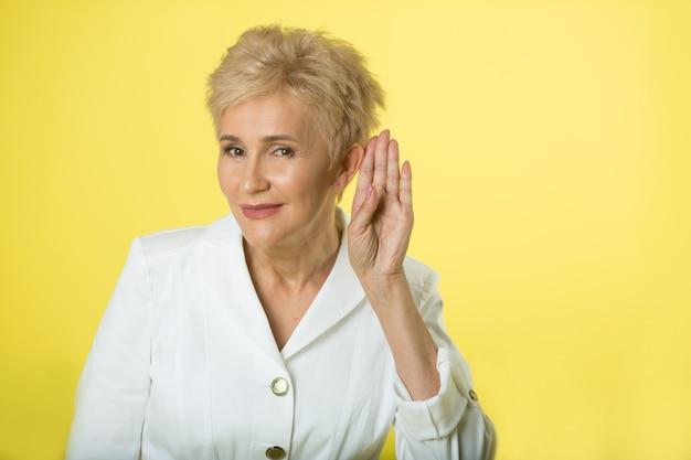 Mooie volwassen vrouw in een jas op een gele achtergrond
