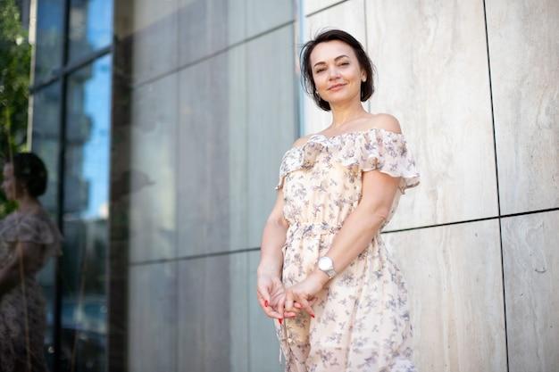 Mooie volwassen vrouw in jurk met klok camera kijken en glimlachen terwijl hand in hand buiten. de plek voor uw ontwerp
