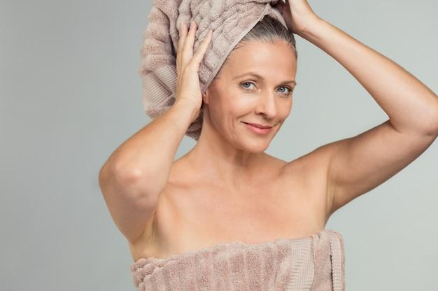 Mooie volwassen vrouw met badhanddoek